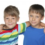 Two smiling little boys are standing together against the white background